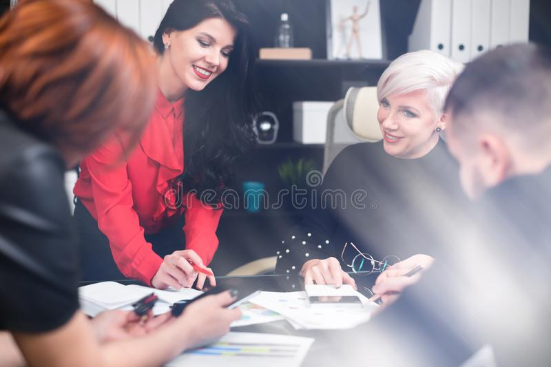 Smiling employees talking in workplace stock photos