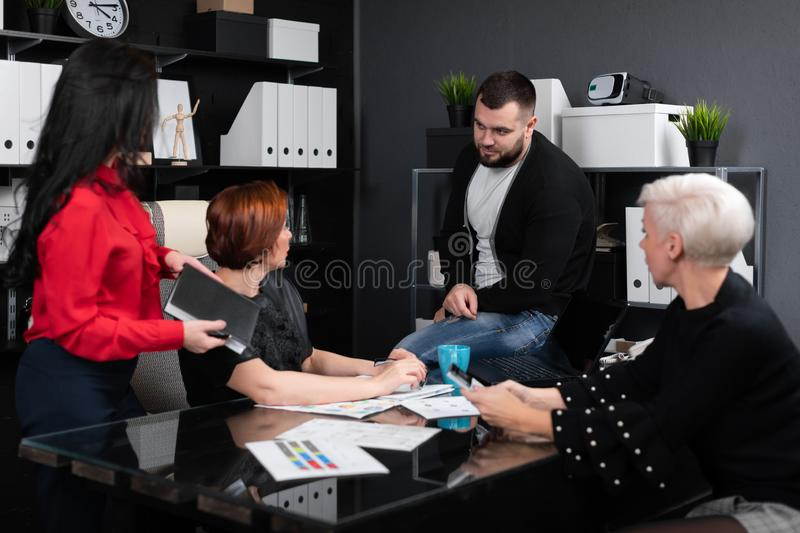 Smiling employees talking in workplace stock photography
