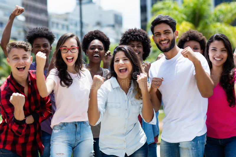 Group of successful cheering latin and caucasian and hispanic and african american young adults. Outdoor in summer in city stock image