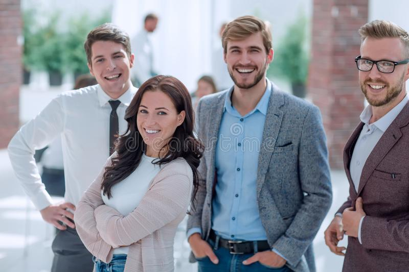 Group of successful young employees standing in the office royalty free stock photography