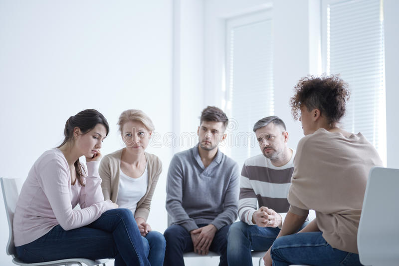 Group supporting sad woman stock photo