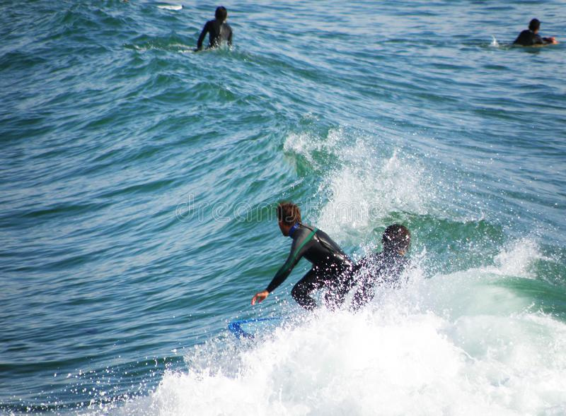 Surfers catching the waves royalty free stock photos