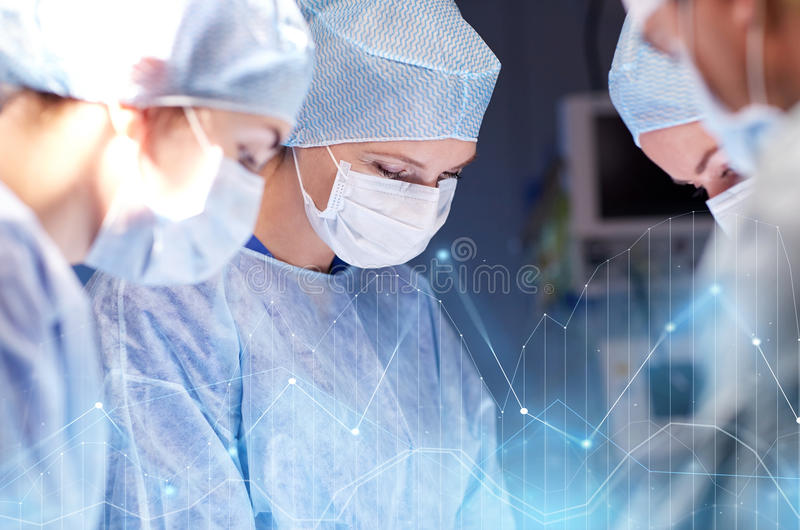 Group of surgeons in operating room at hospital stock photography