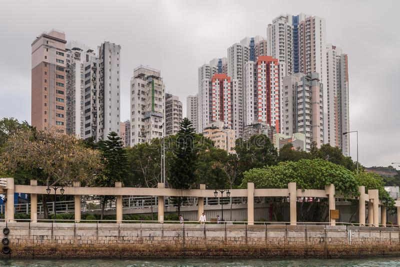 Group of tall buildings on shore of harbor of Hong Kong, China. Hong Kong, China - May 12, 2010: Group of tall apartment buildings on shore of harbor. Foggy stock photo