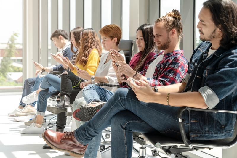 Group of technology team sitting and using smartphone digital gadget. Young asian diversity creative business team are waiting and stock photography