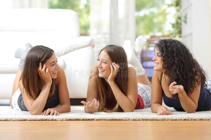 Group of teen friends talking at home. Group of happy teen friends talking lying on the floor at home royalty free stock image