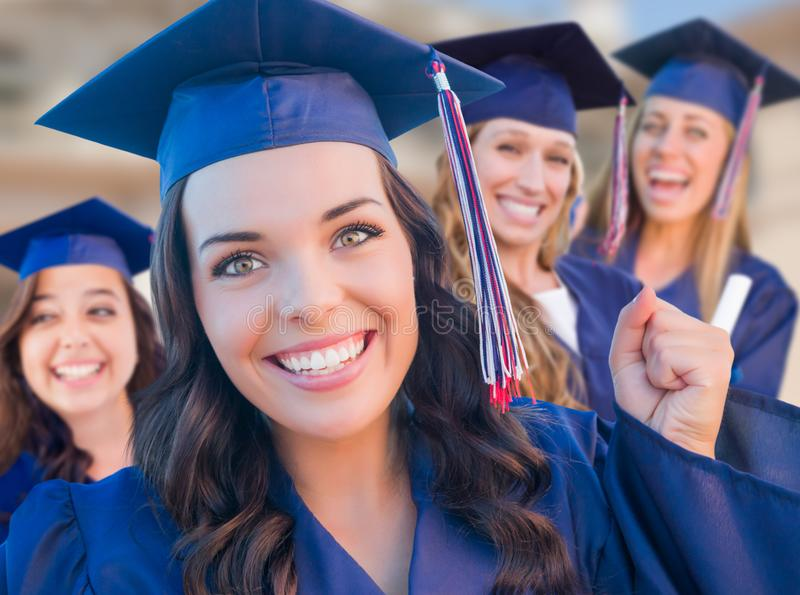 Group of Teen Girls Graduating In Cap and Gown on Campus. Happy Graduating Group of Girls In Cap and Gown Celebrating on Campus stock images