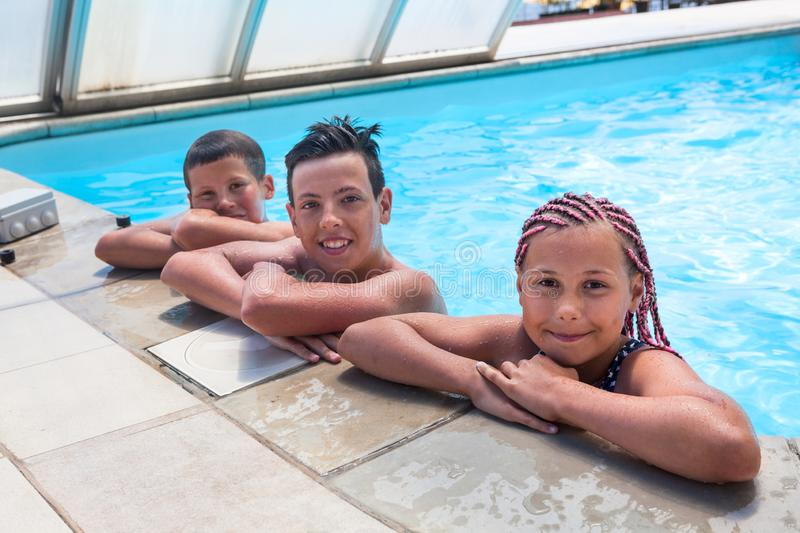 Group of teenage children enjoy swimming in pool, two boys and one girl looking at camera royalty free stock photo