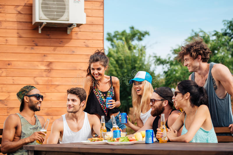 Group of teenage friends drinking beer and eating snacks. Happy group of teenage friends sitting at table drinking beer and eating snacks royalty free stock photo