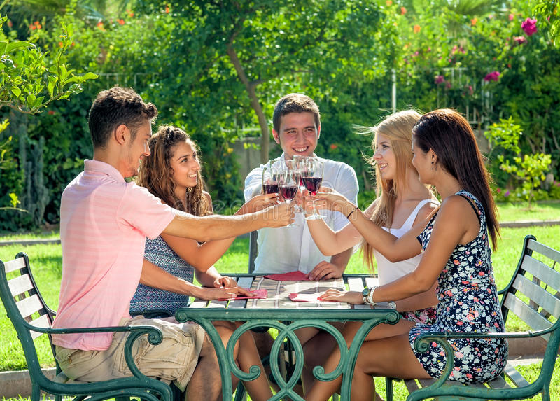 Group of teenage friends enjoying a drink together stock photography