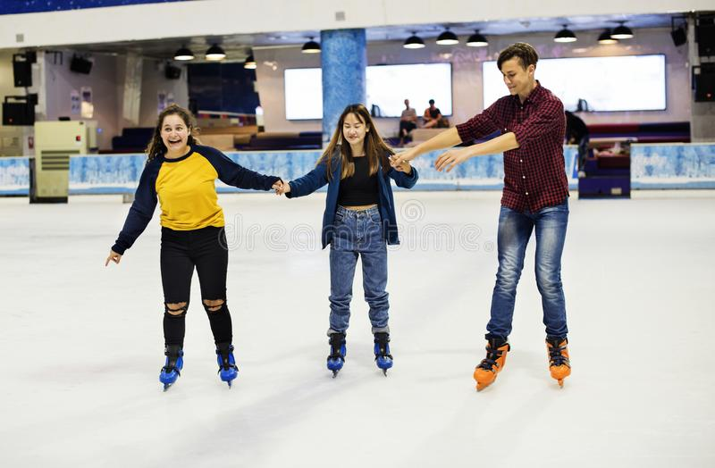Group of teenage friends ice skating on the ice rink together royalty free stock image