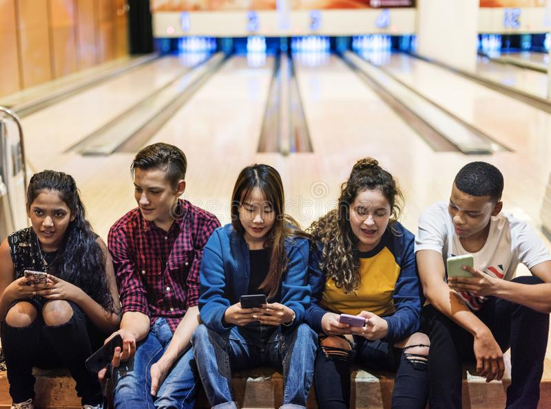 Group of teenage friends using smartphone in a bowling alley royalty free stock photography