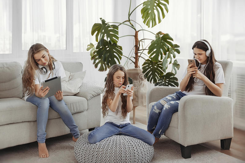 Group of teenage girls is using gadgets. Kids with phones and tablets, smartphones and headphones. Group of teenage girls is using gadgets. Kids with phones and royalty free stock photo