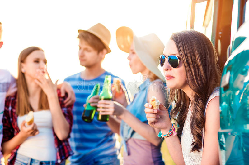 Group of teenage hipsters on roadtrip, drinking beer, eating royalty free stock image