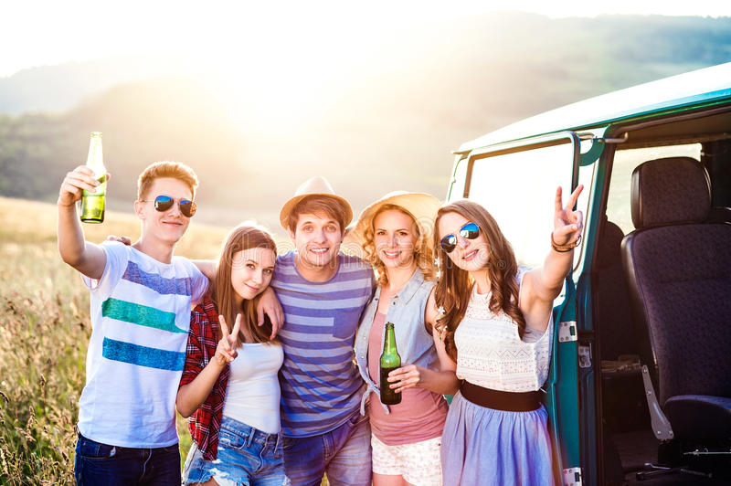 Group of teenage hipsters on a roadtrip, drinking beer royalty free stock photos