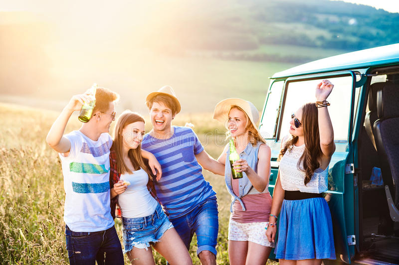 Group of teenage hipsters on a roadtrip, drinking beer royalty free stock photography