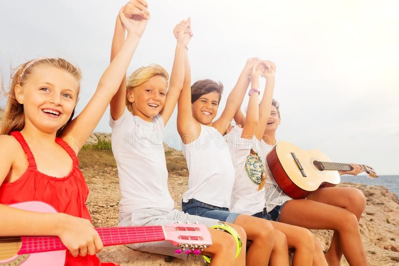 Happy friends with guitar having fun on the beach stock image