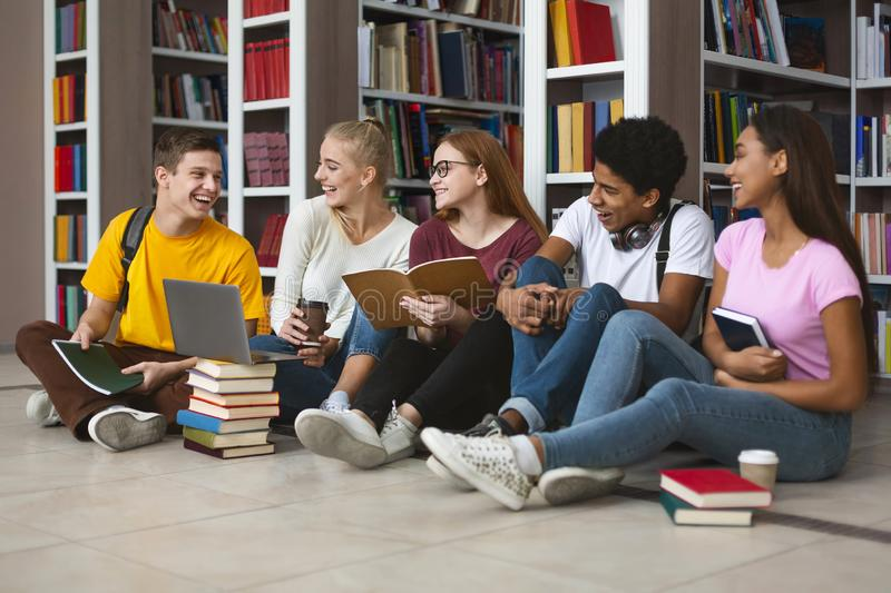 Group of teenage students making homework and smiling. Group of international tennage friends making homework and smiling, library interior, free space stock photos