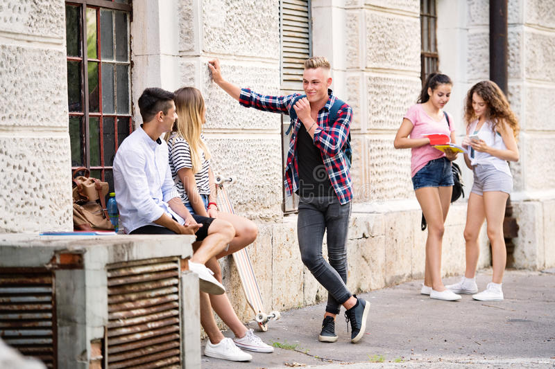 Group of teenage students talking in front of university. stock photo
