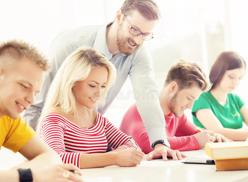 Group of teenage students and a teacher at the lesson in the classroom. Education, school, college and university concept. Hipster color stock images