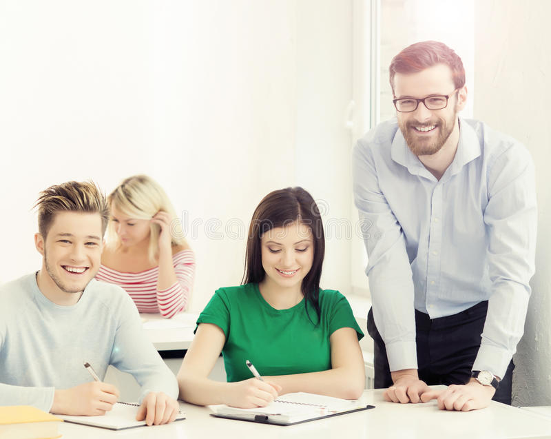 Group of teenage students and a teacher at the lesson in the classroom. Education, school, college and university concept. Hipster color royalty free stock image