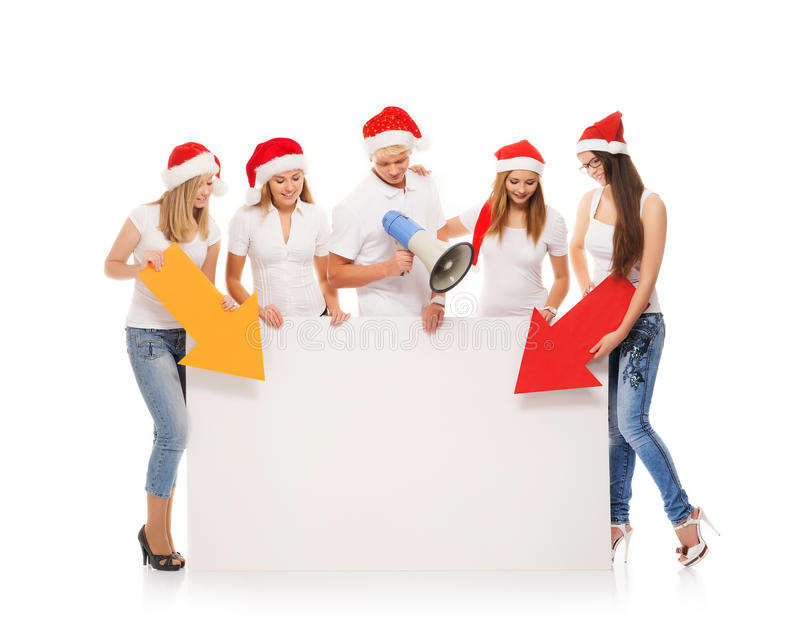 A group of teenagers in Christmas hats pointing on a blank banner and using a megaphone royalty free stock photos