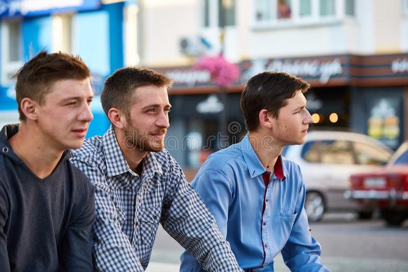A group of teenagers hanging out outside in the city on the retro background royalty free stock photography