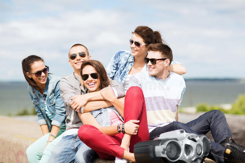 Group of teenagers hanging out. Summer holidays and teenage concept - group of teenagers hanging out royalty free stock photo