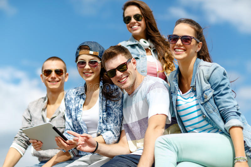 Group of teenagers looking at tablet pc computer. Summer holidays, teenage and technology concept - group of teenagers looking at tablet pc computer outdoors stock photography