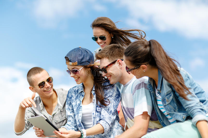Group of teenagers looking at tablet pc computer. Summer holidays, teenage and technology concept - group of teenagers looking at tablet pc computer outdoors royalty free stock images