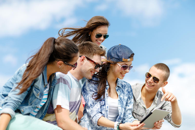 Group of teenagers looking at tablet pc computer. Summer holidays, teenage and technology concept - group of teenagers looking at tablet pc computer outdoors stock image