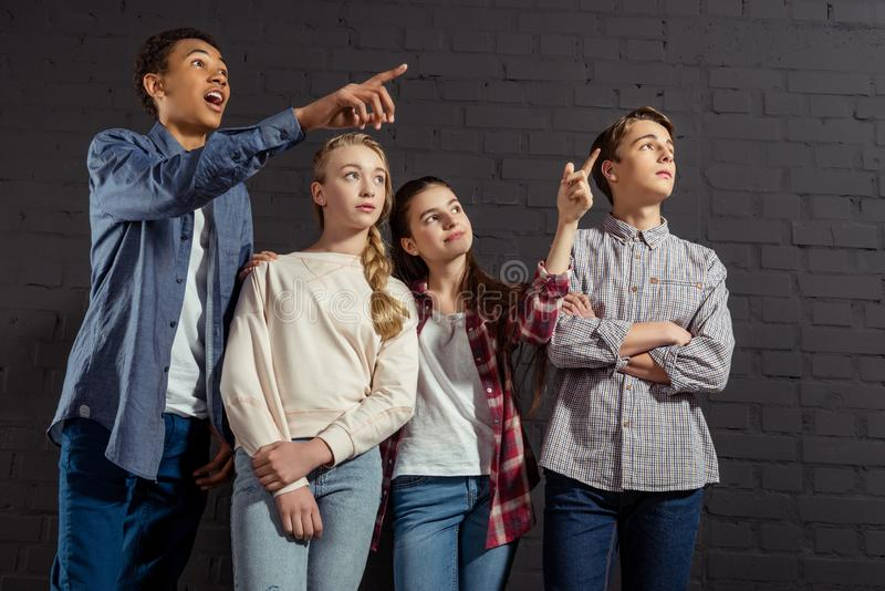 group of teenagers pointing somewhere in front of black stock image