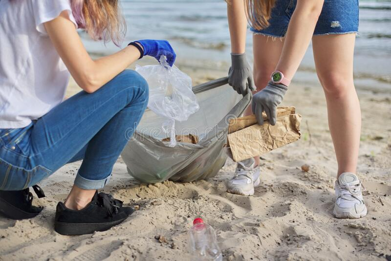 Group of teenagers on riverbank picking up plastic trash in bags. Environmental protection, youth, volunteering, charity, and ecology concept stock photo