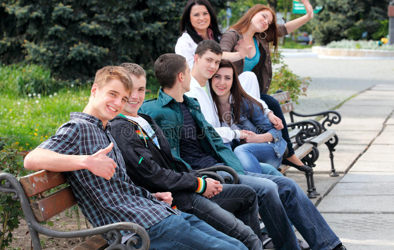 Group of teenagers sitting outside stock images
