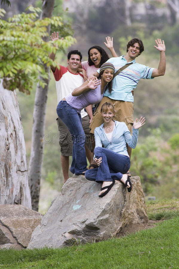Group of teenagers (17-19) standing on top of rock, waving, smiling, portrait stock photography
