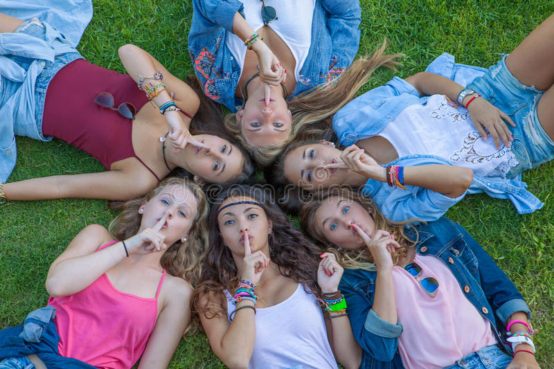 Group of teens fingers to lips for suprise secret. stock photography