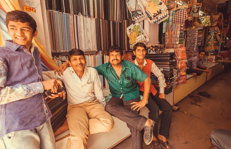 Group of textile market traders relaxing near traditional male and female clothing stores royalty free stock photo
