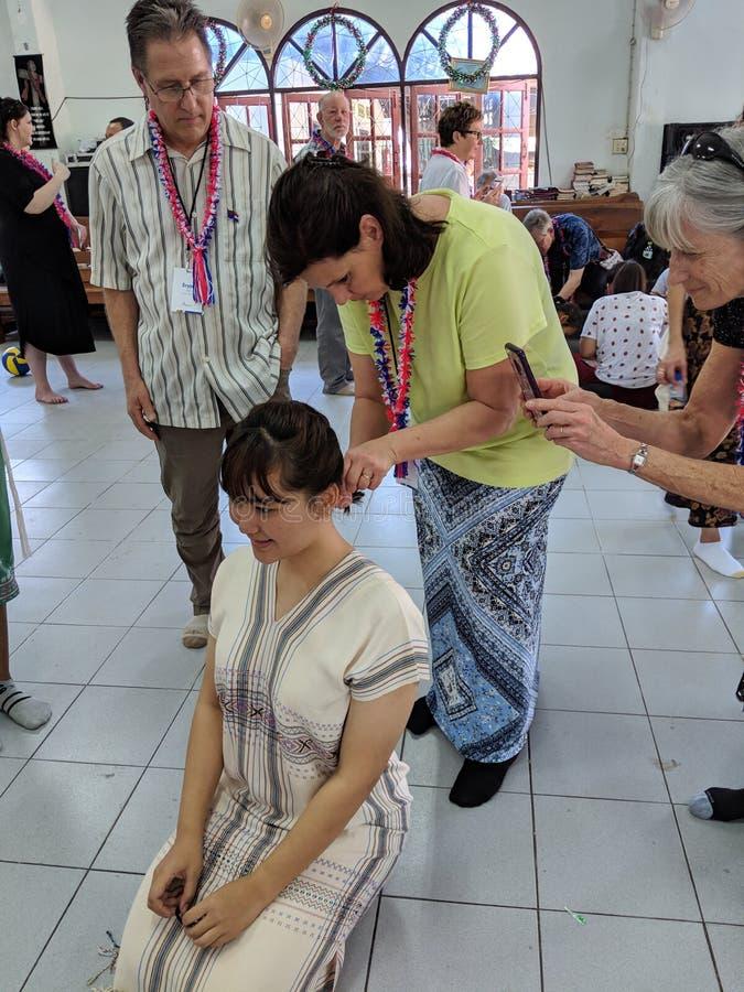 Caucasian woman braiding hair for Thai teenage girl on trip to Thailand. royalty free stock photography