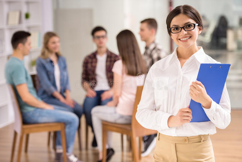 Group therapy. Serious female therapist with group therapy in session in background stock photography