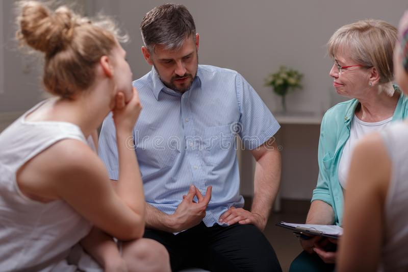 Group therapy session. Businessman talking about his problems during group therapy session royalty free stock photo
