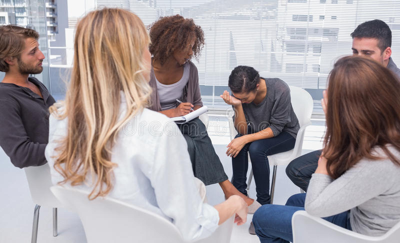Group therapy session with one woman crying. Group therapy session with one women crying in therapists office stock images