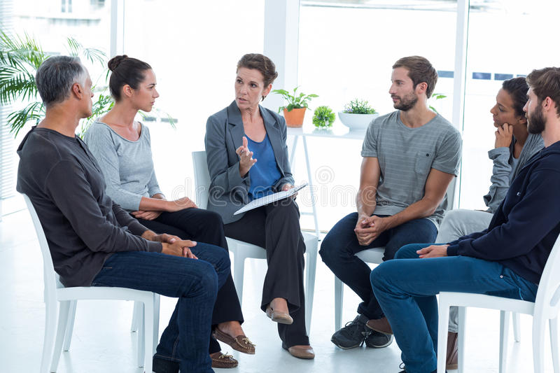 Group therapy in session sitting in a circle. In a bright room royalty free stock photo