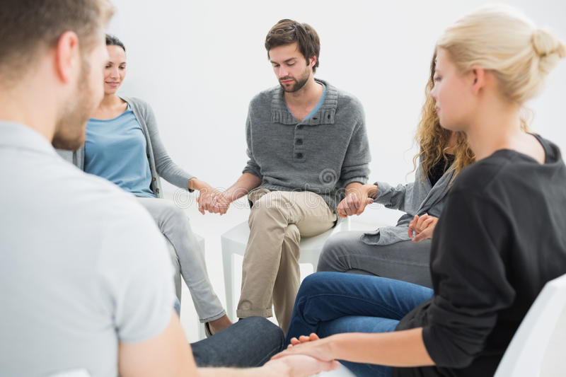 Group therapy in session sitting in a circle. With therapist stock photo