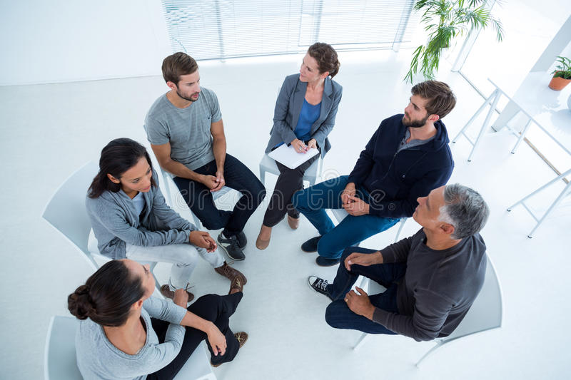 Group therapy in session sitting in a circle. Upward angle view of a therapy group in session sitting in a circle in a bright room royalty free stock image