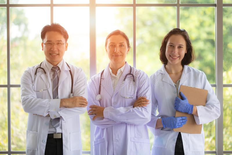 Group of thfee doctors standing near big window with sunlight in behind. Concept for team work in hospital and healthcare business royalty free stock images