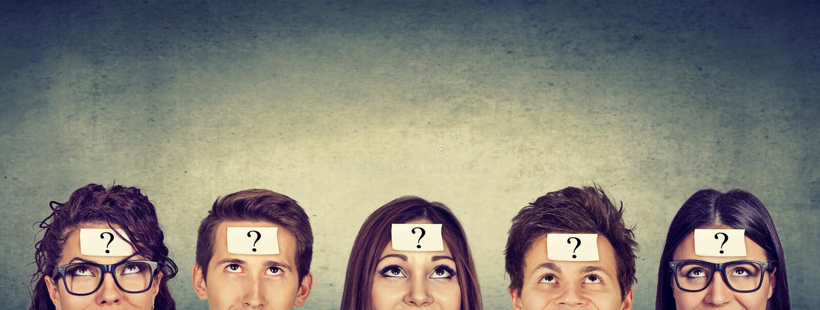 Group of thinking people with question mark looking up stock image