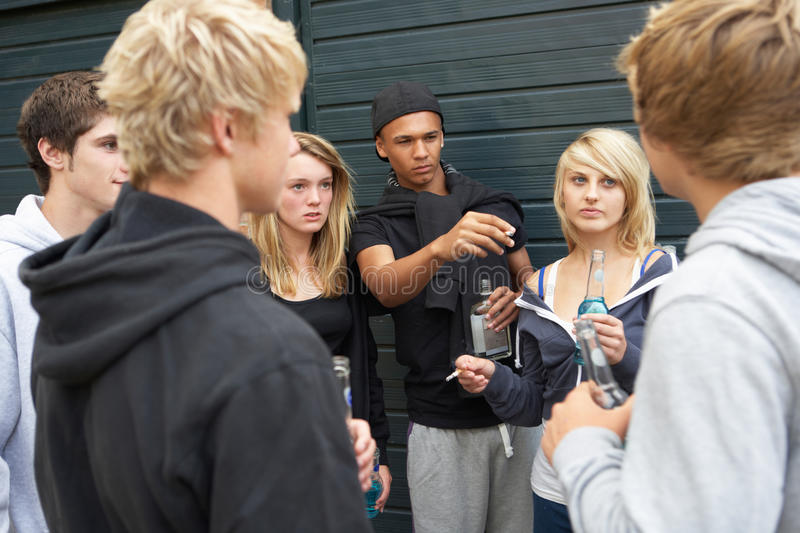 Group Of Threatening Teenagers Hanging Out. Together Outside Drinking royalty free stock image