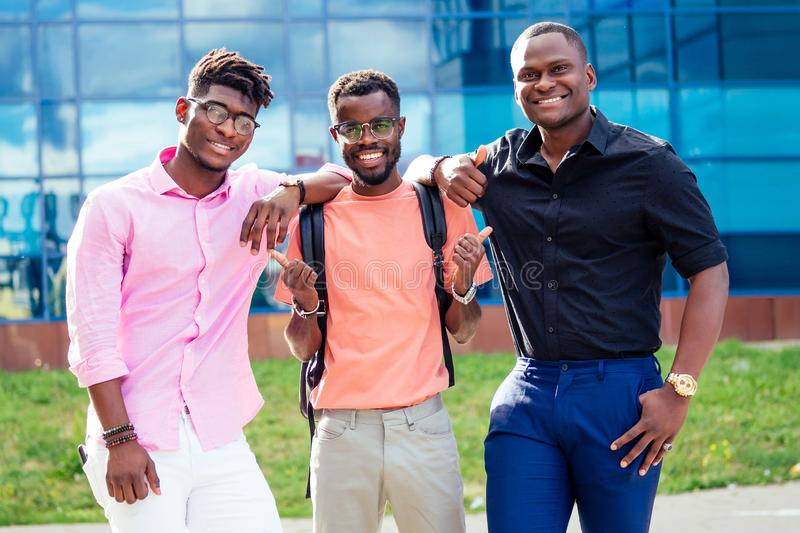 A group of three African Americans male friends in stylish clothes stand against the background of the blue windows of stock photo