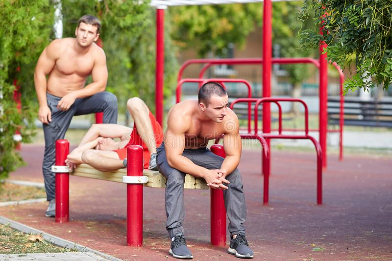 Three muscular men relaxing on a training area background. Training concept. Copy space. stock photos