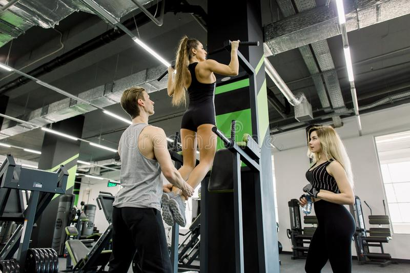 Group of three attractive young male and female adults in gym. Young girl doing pull ups on bar in cross fit training stock photos
